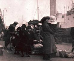 Families waiting to depart at the docks near their ship..