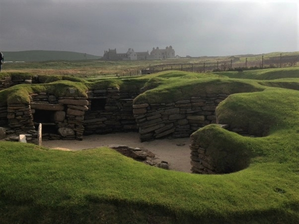 Skara Brae, situated on the Bay of Skaill, is a neolithic farming settlement from circa 4,500 years ago. It is the best preserved prehistoric village in Northern Europe as the houses still contain the main items of furniture. Today 7 houses and a workshop remain, built mainly of stone, these are linked by passages to form a tight-knit community. Skaill House is in the background.