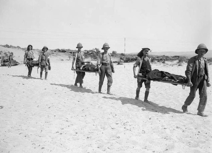 Stretcher bearers taking the wounded off the beaches, Gallipoli 1915. Hospital ships were waiting out at sea but these vessels were often overcrowded and the wounded had long delays for treatment.