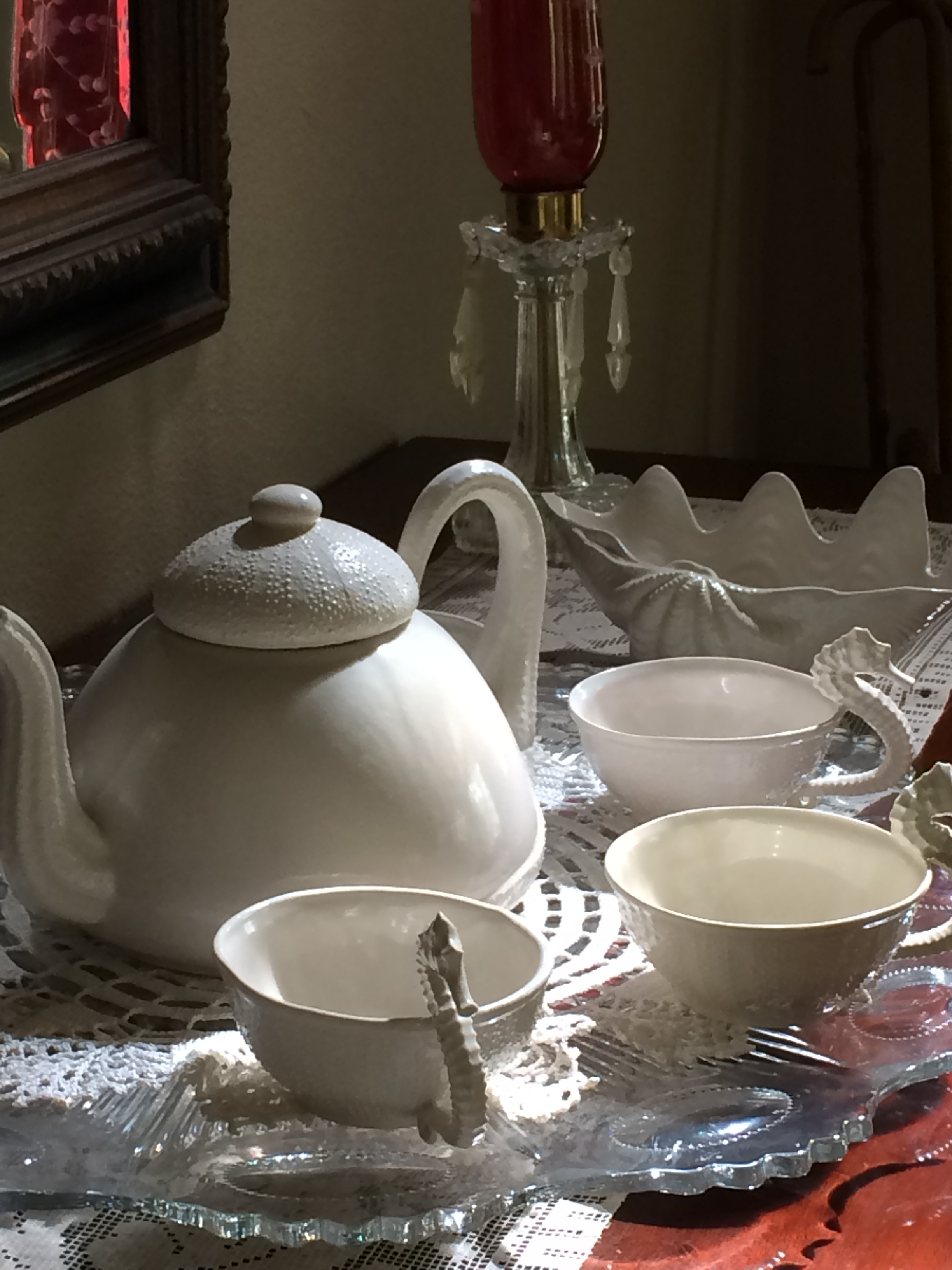 Porcelain Teacups surround a Made in USA Porcelain Teapot in the sunlight