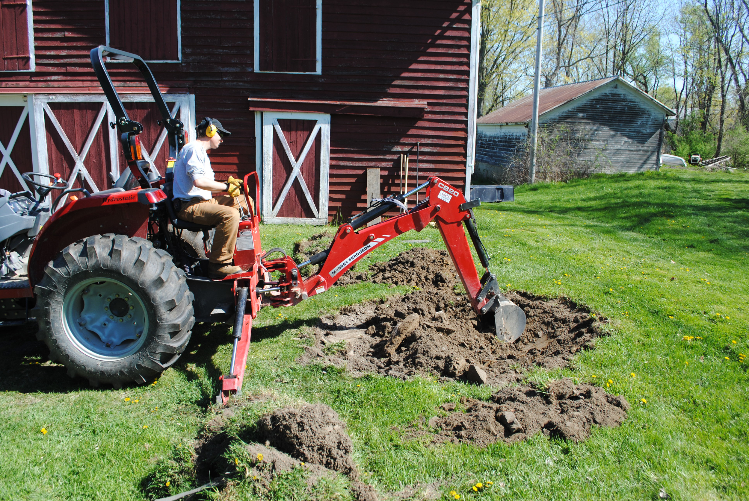 Arborist Peter Madsen digs a planting hole in preparation for planting a spruce tree.