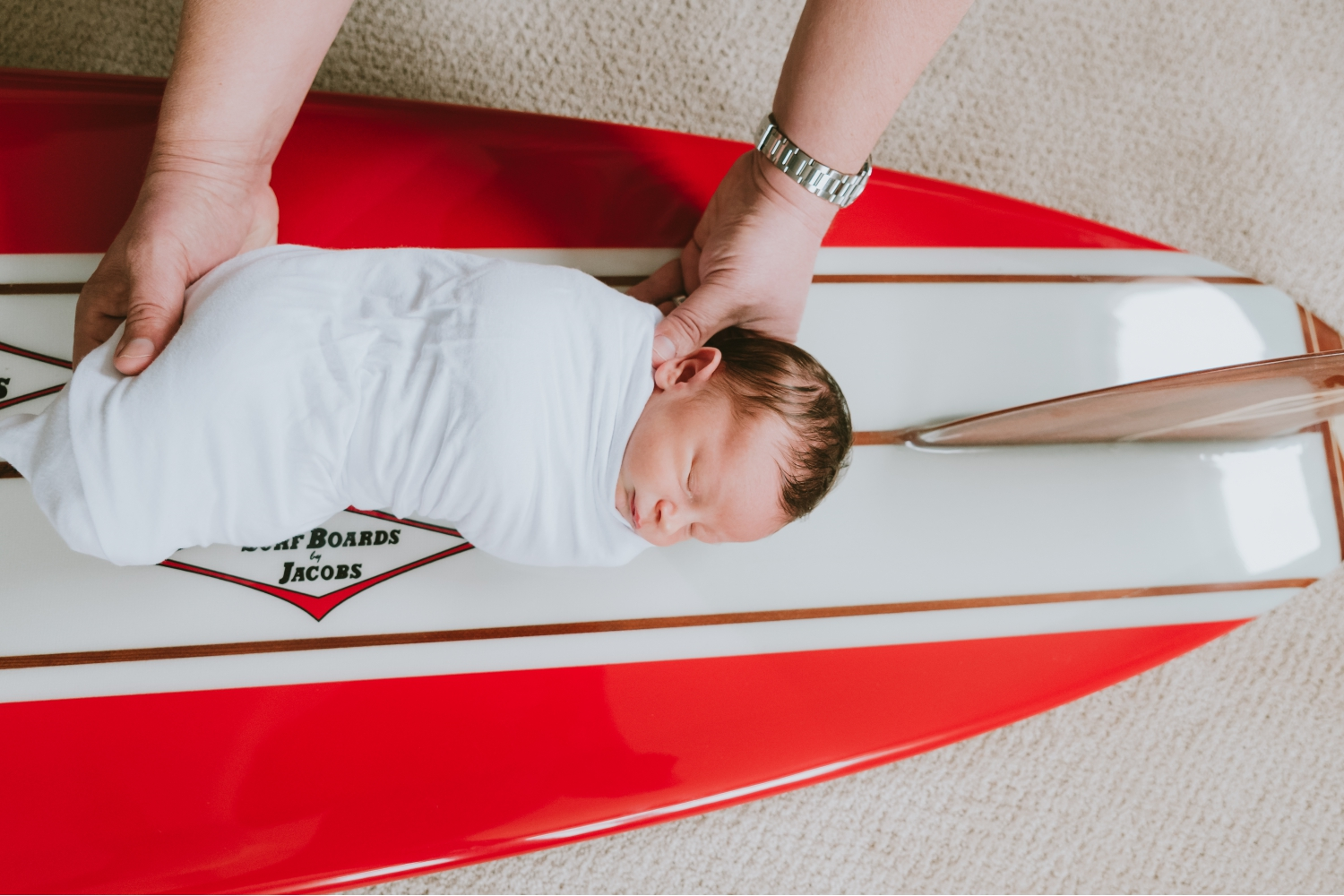 Picture-Of-Dad-Holding-Newborn-Baby-Boy-On-Custom-Surf-Board-During-Newborn-Pictures-Ocean-County-New-Jersey