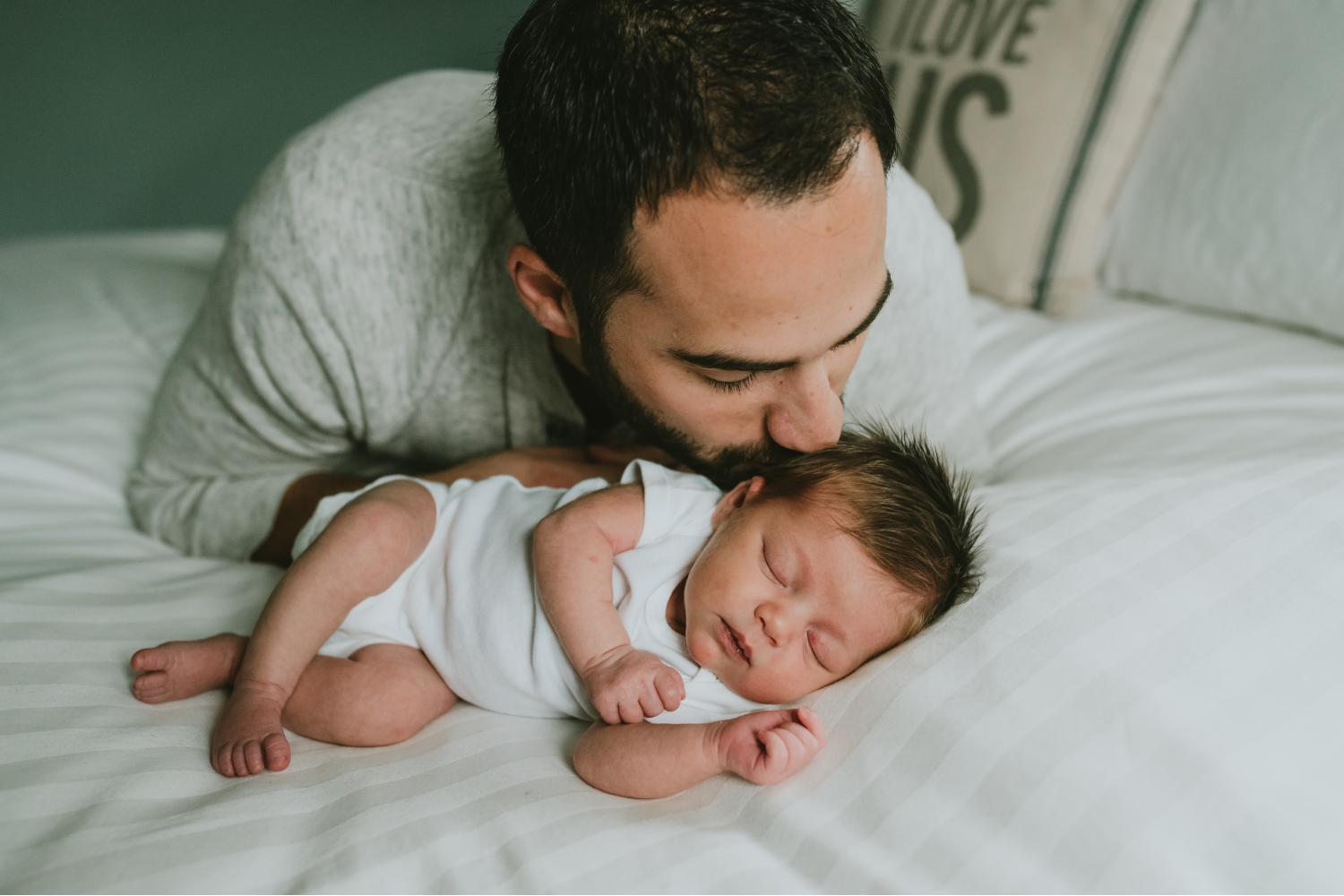 Daddy-Kissing-Newborn-Daughter