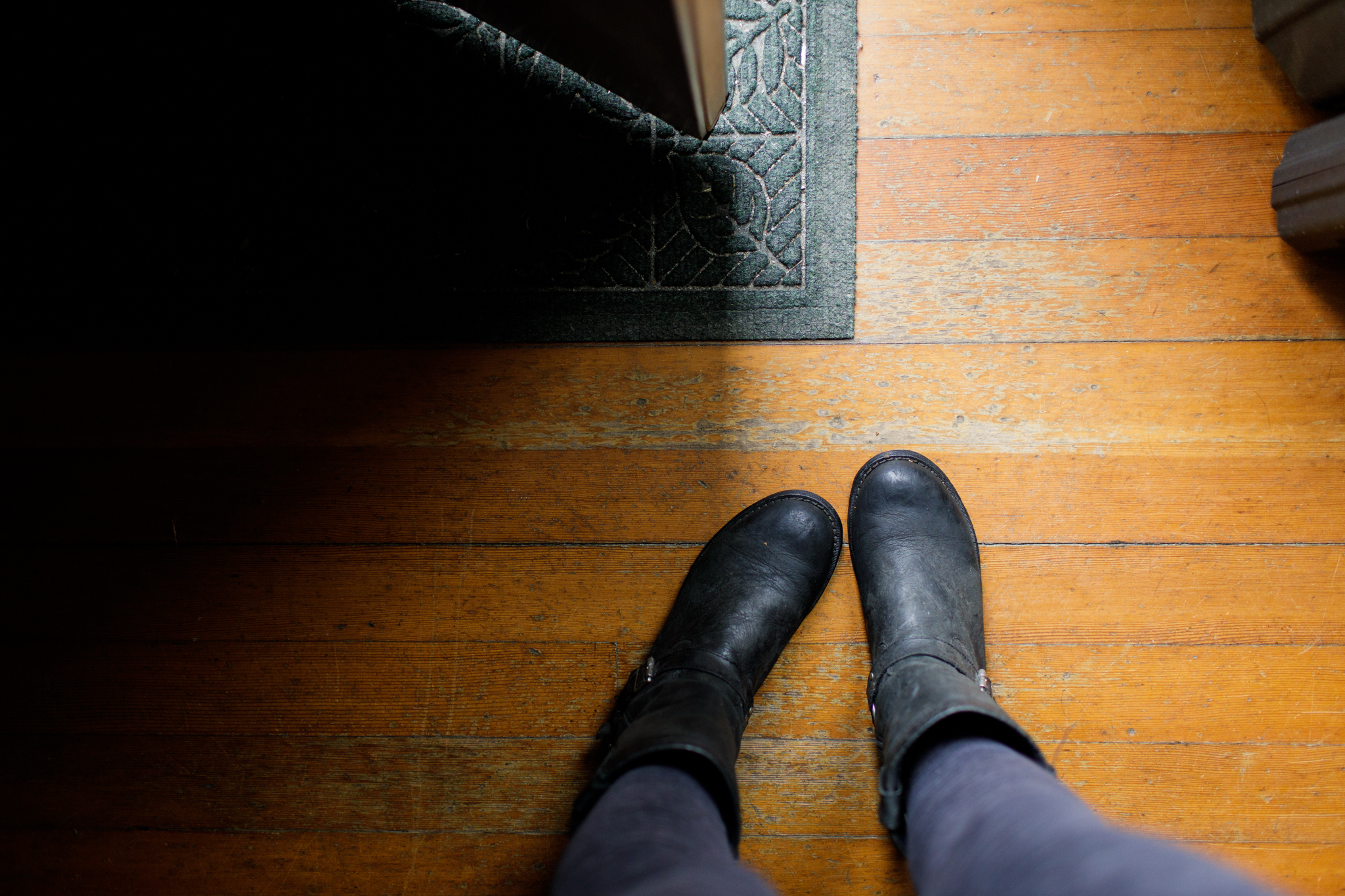 image of woman's legs and boots, standing in a doorway, taken from above