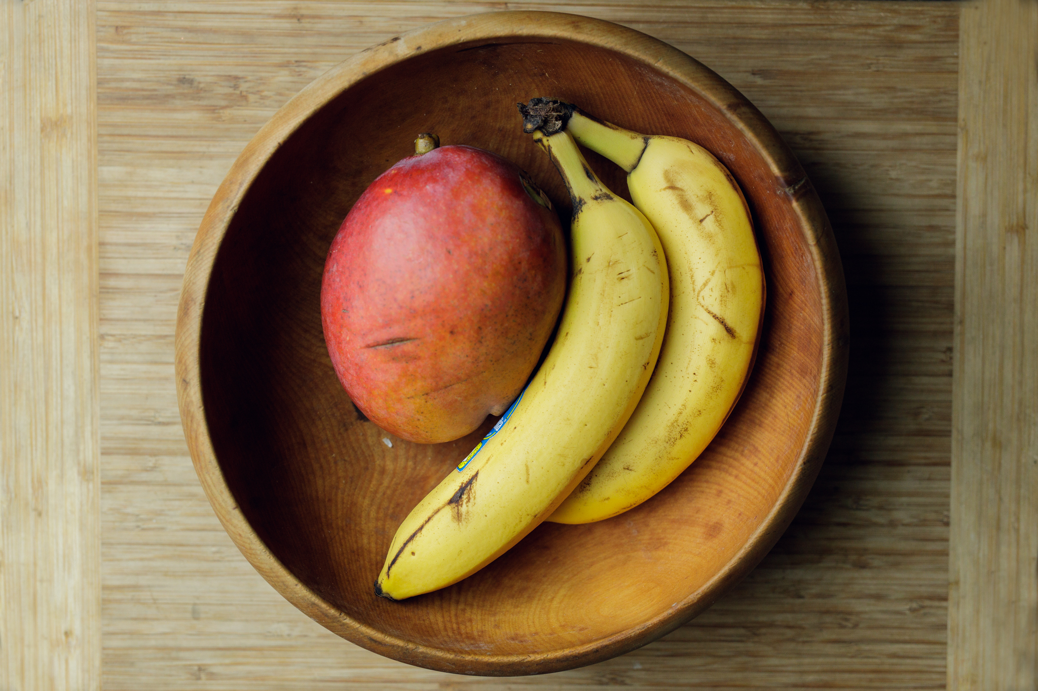 bananas and mango in a wooden bowl