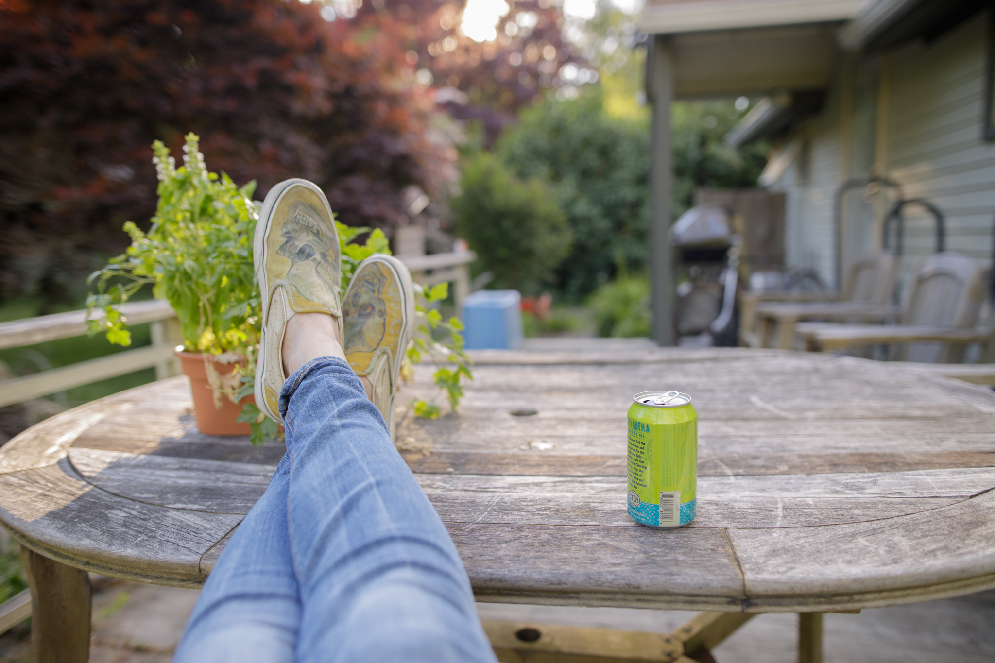 woman sitting at patio table with plant and beer