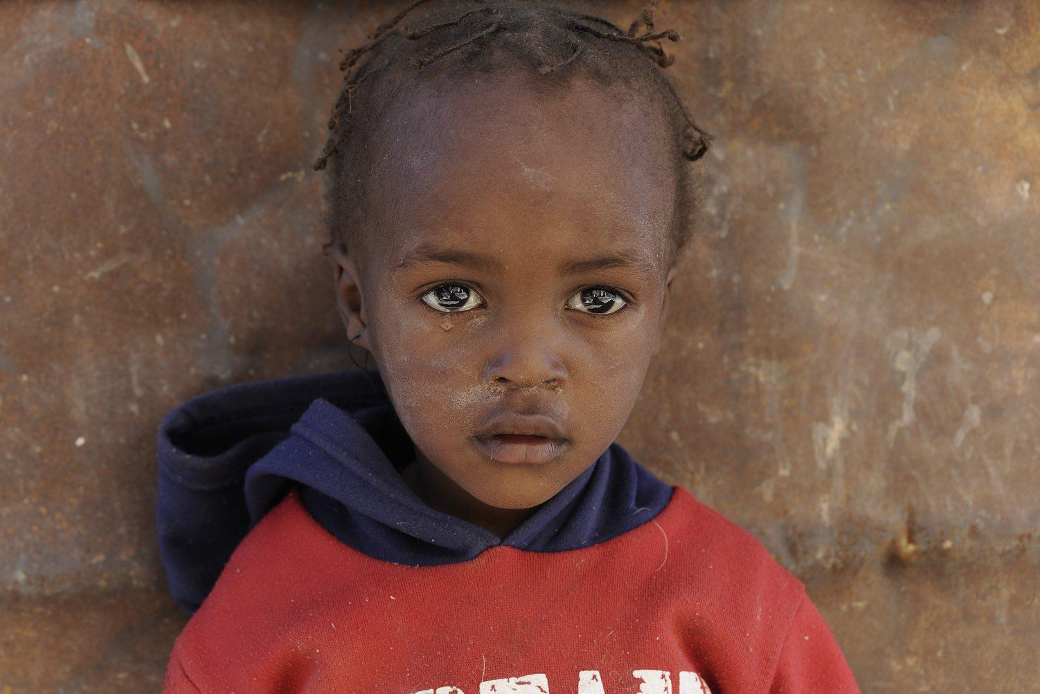 COA-by-Thijs-9  Jason Swartbooij (2) woont samen met zijn oma Theresia (43) en nog een paar kinderen in een eenvoudige hut in het droge en afgelegen zuiden van Namibië. De man van Theresia werkt op een boerderij in de buurt. Ik ontdek het mooie en liefdevolle gezin toevallig als ik op zoek ben naar een zuidelijke toegang tot de Fish River Canyon. Een paar jaar later ben ik terug geweest naar deze plek om het gezin wat geld te geven om een eigen huis te bouwen. Voor zover ik heb kunnen nagaan is dat ook werkelijk gelukt, in een stadje niet ver van de plek waar ik ze ontmoette.