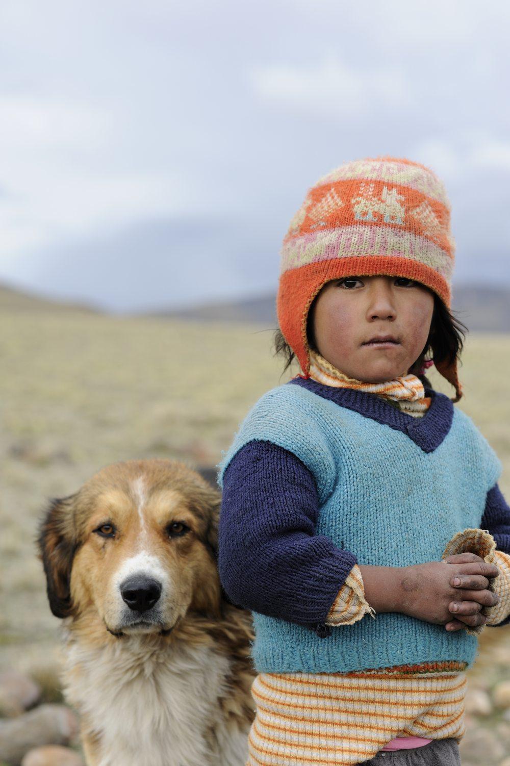 COA-by-Thijs-7  Hoog in de bergen in Peru, ten zuiden van Cuzco, stuitte ik op een kudde alpaca's die door twee jongetjes en een paar honden werd gehoed. Toen we de auto stopten en een paar foto's van de schitterende omgeving maakten, kwamen de herders en hun honden enthousiast aangerend. We hebben een paar minuten met elkaar gepraat en ergens tijdens die bijzondere ontmoeting maakte ik dit portret.