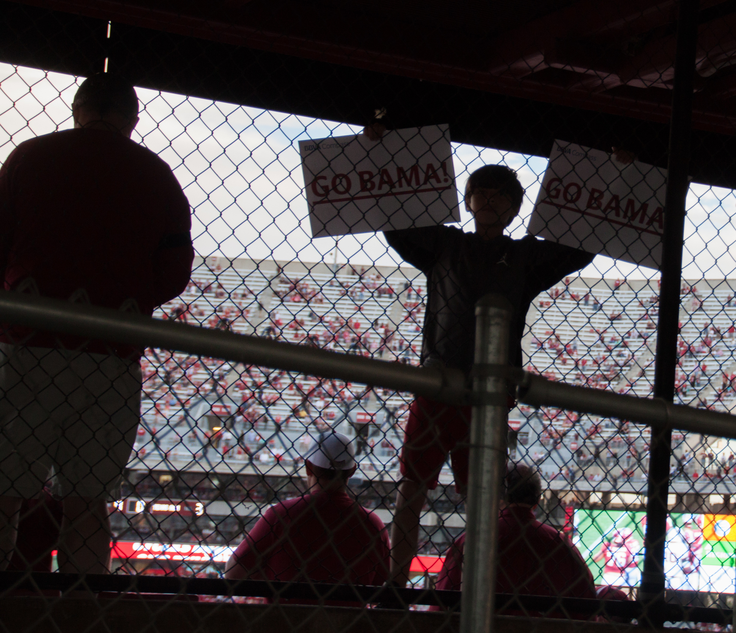 """While leaving the stadium I caught this fan holding up """"GO BAMA!"""" signs. Needless to say that phrase """"Roll Tide!"""" was said a few times."""