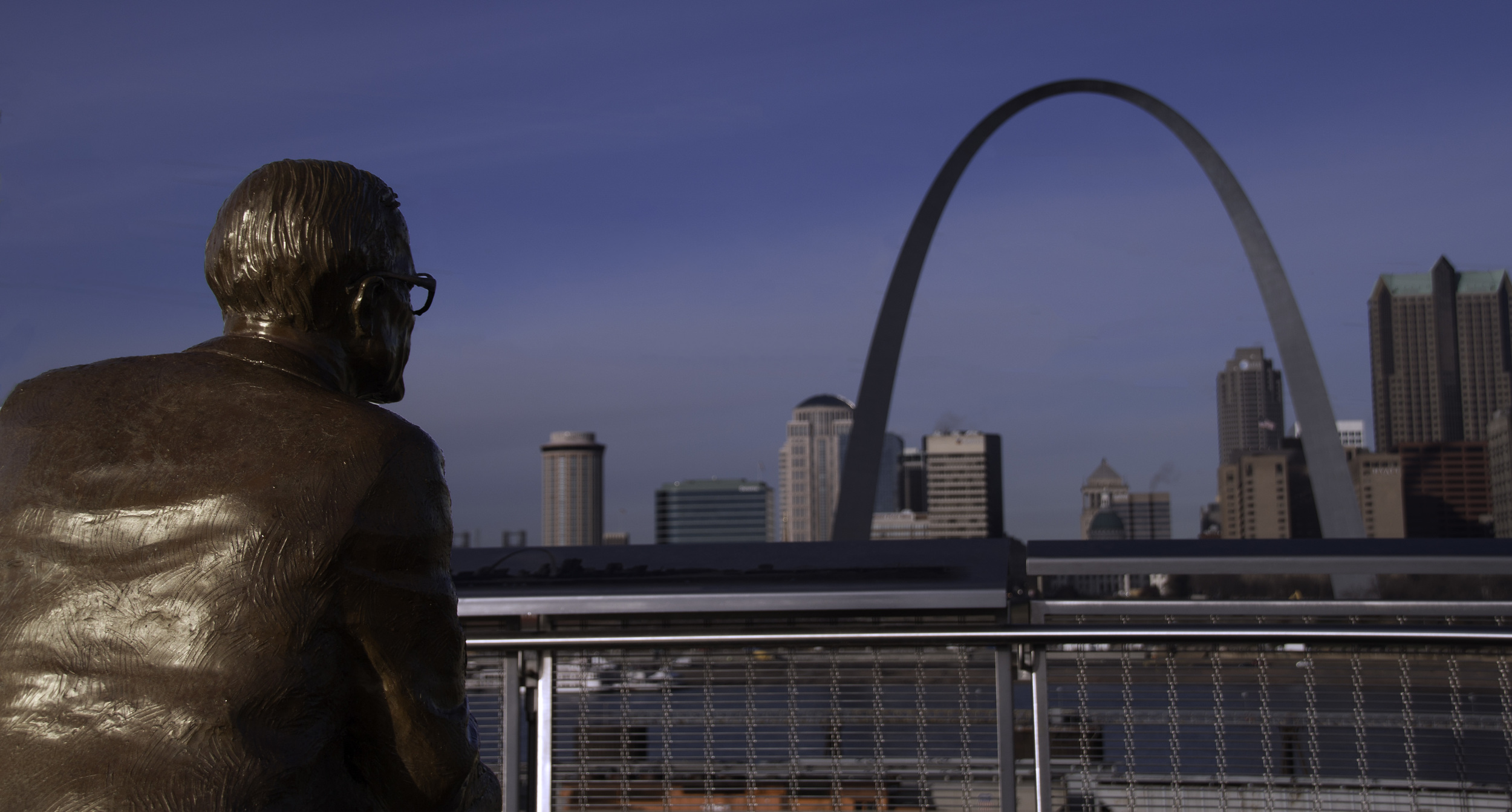 A shot behind the Malcom Martin Statue looking across the Mississippi River at the Gateway Arch