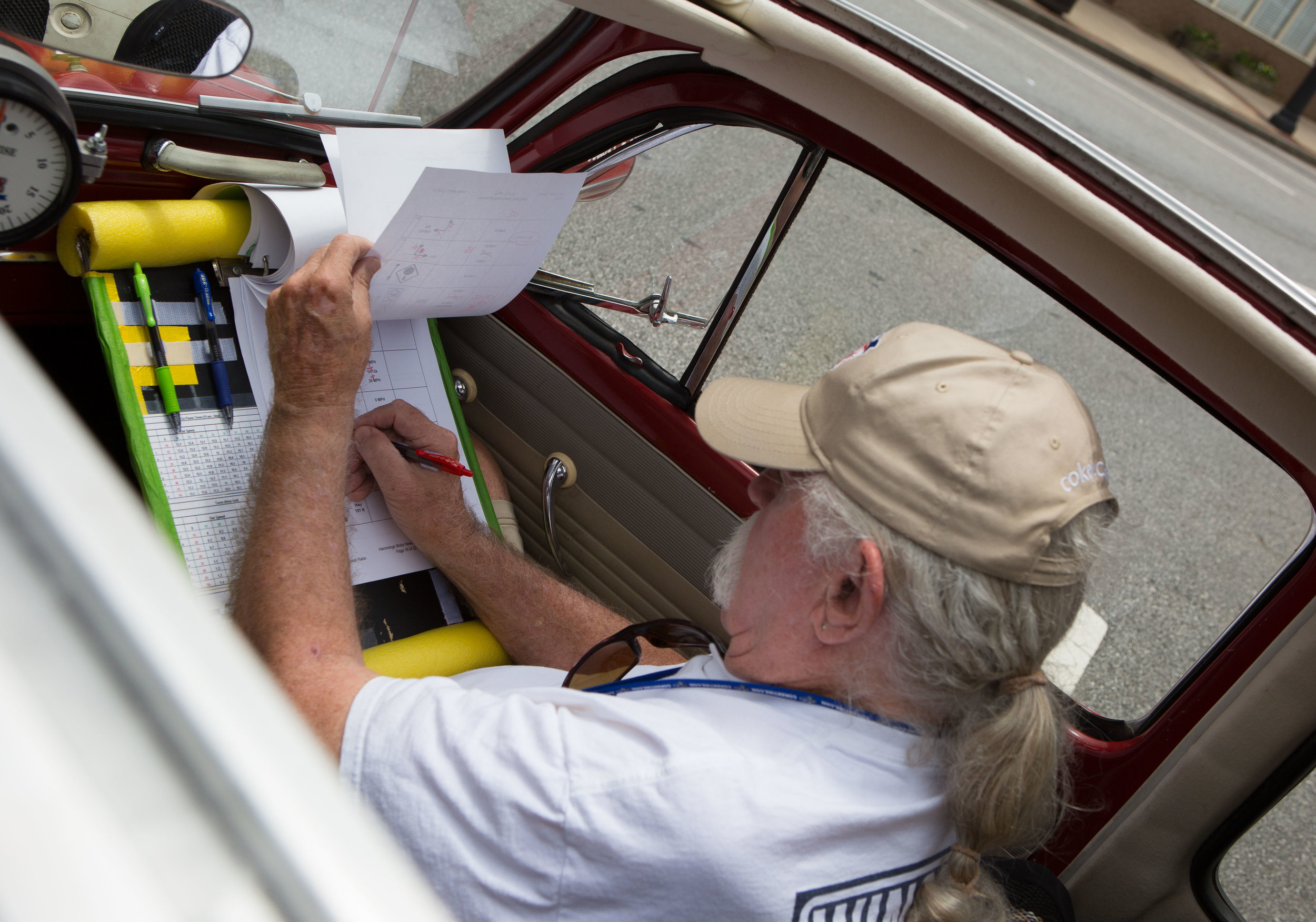 Great Race car #61 Navigator Bruce Bernbaum works on navigation plans during during The Great Race lunch stop in Newnan, GA.