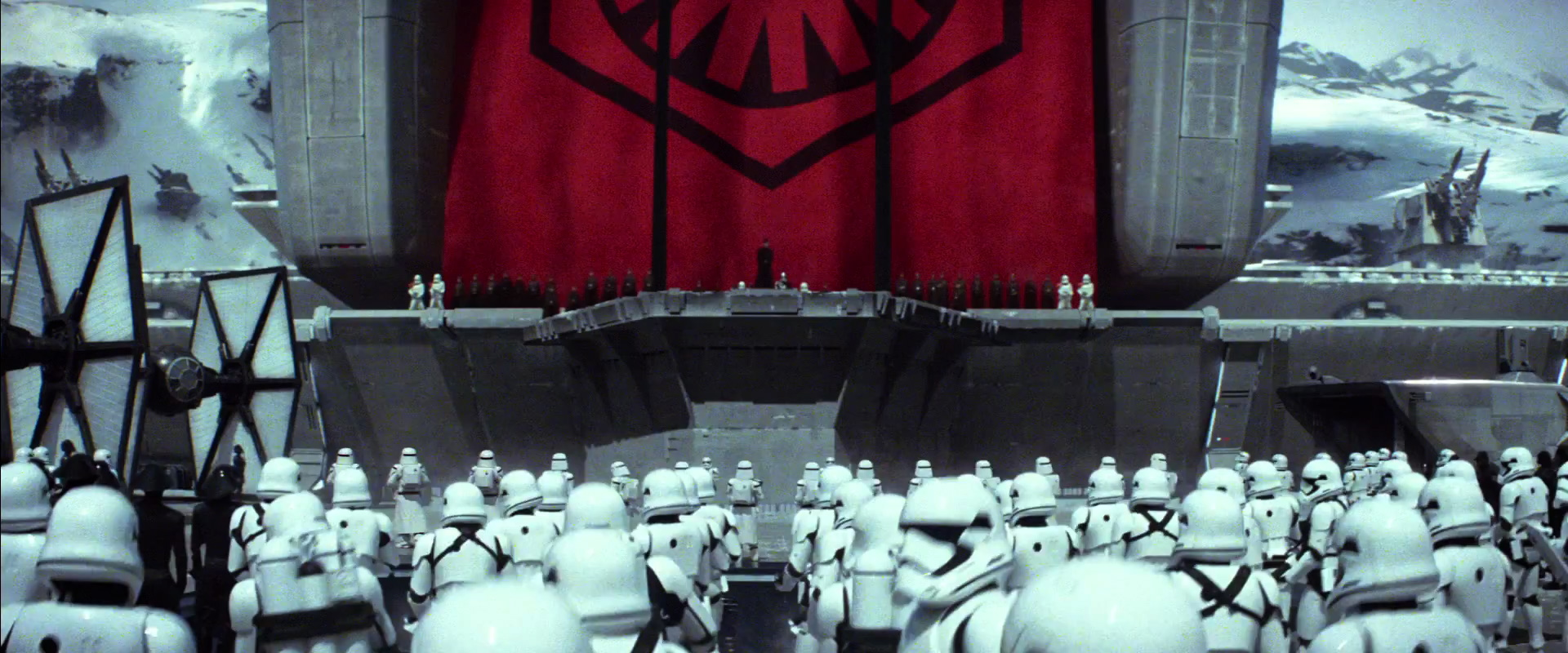 """The Empire also has a new name """"The First Order."""" They also have a new symbol. Who ever is on stage must be important. Lots of speculation on who it is but It's all guesses.  On the left side a black Tie Fighter with white panels that some are calling Inverted Ties or Stealth Ties; I'm just going to call them New Ties until we know for sure."""