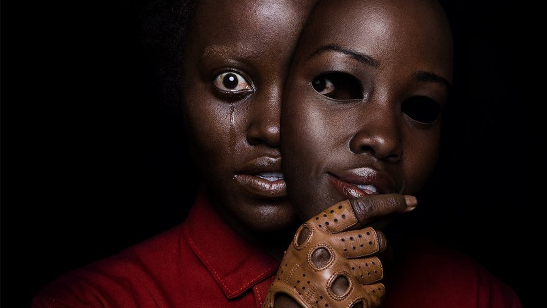 unsettling-new-poster-for-jordan-peeles-us-features-lupita-nyongo-holding-a-mask-of-her-own-face-social.jpg