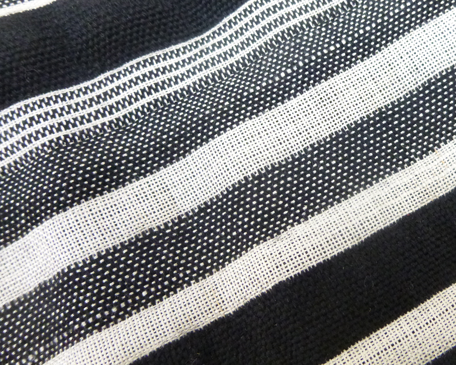 Hand woven on Texel dobby loom using an alternating (end on end) warp of black wool  and matural silk warp.