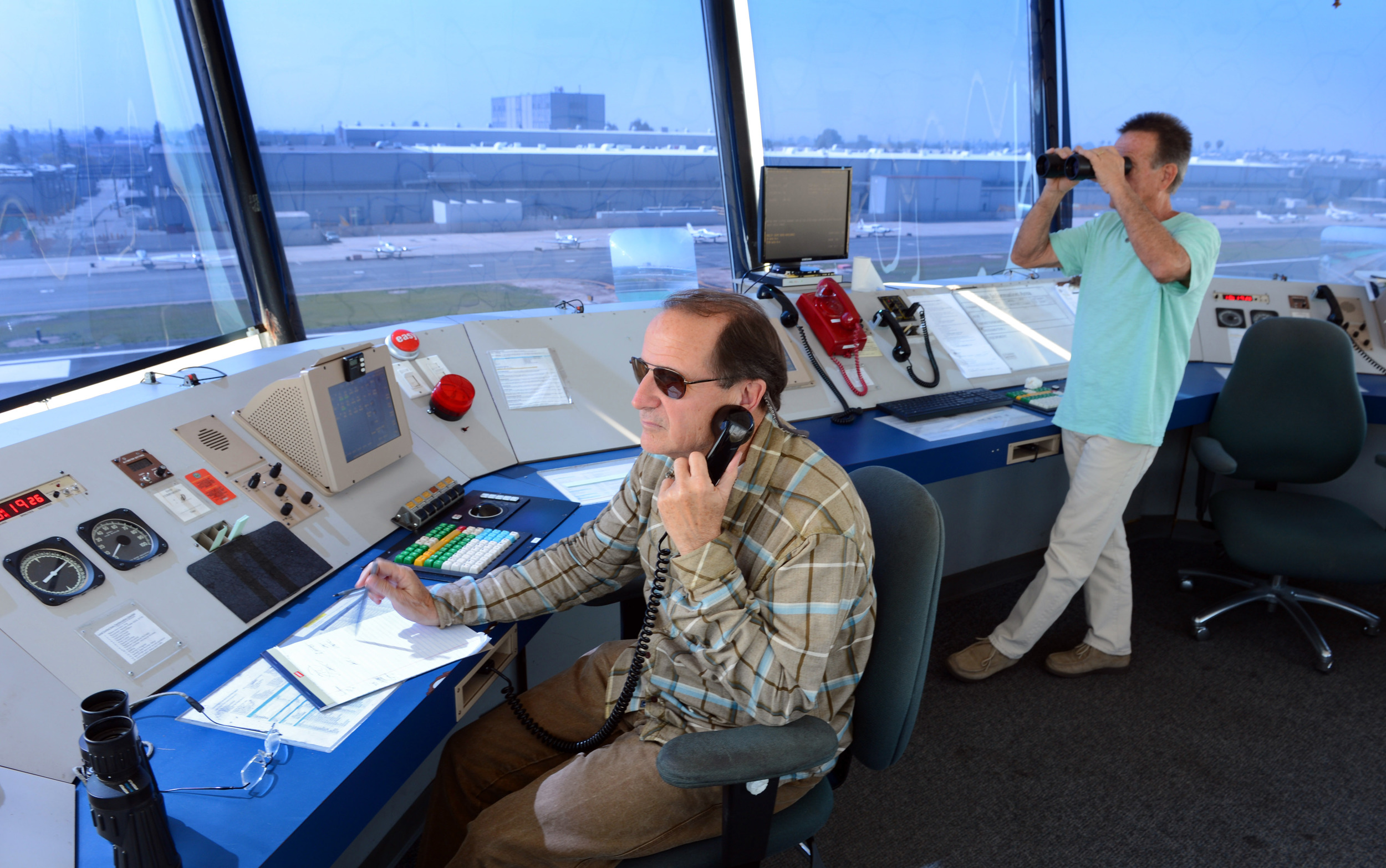 Air traffic controllers Tom Morris, left, and Derk Kuyper monitor activity at the Hawthorne Airport in this March 2013 photo. (Brad Graverson / Staff Photographer)