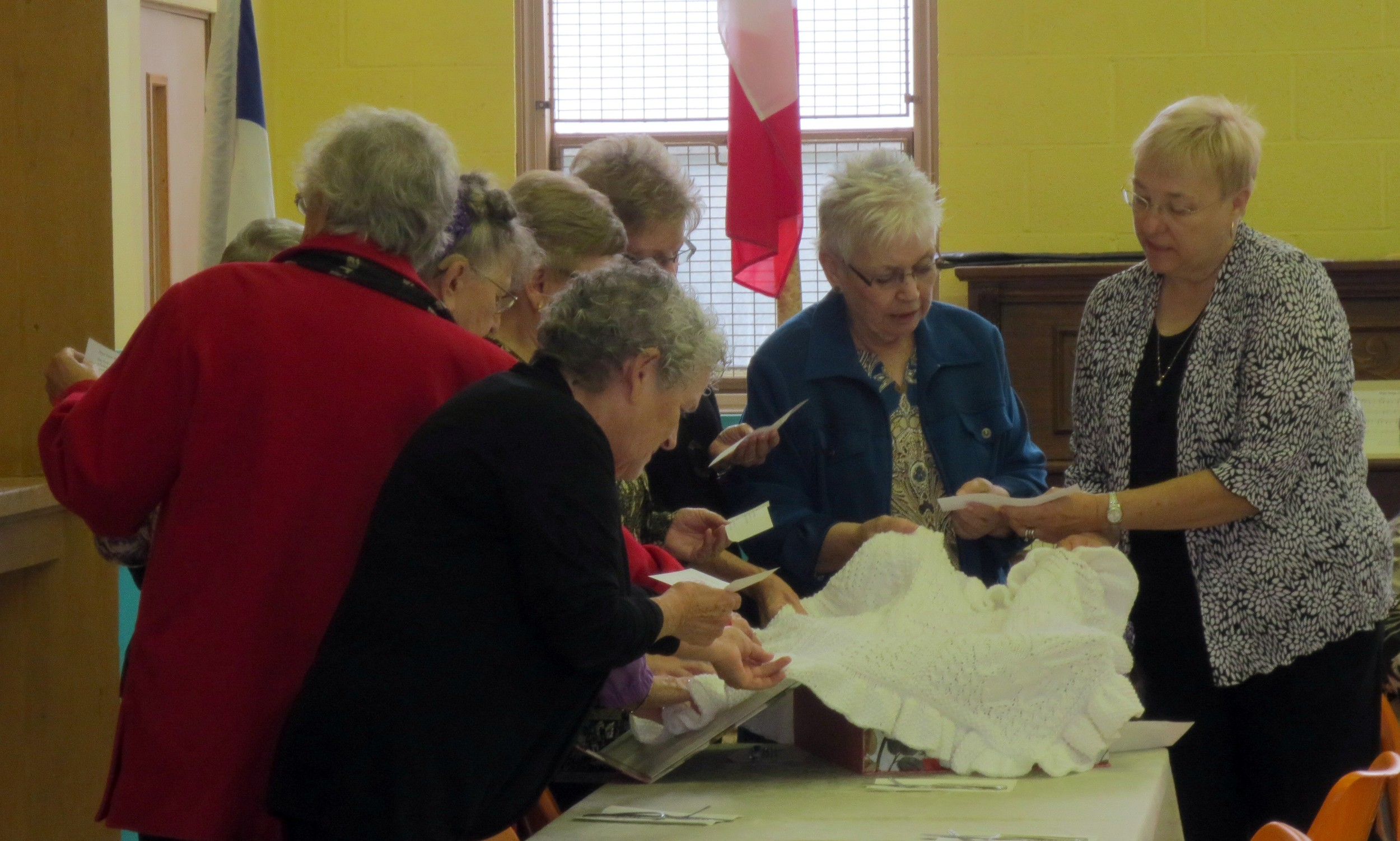 Ladies from the Prayer Shawl Ministry blessing the shawl that was made for Pastor Heidi.