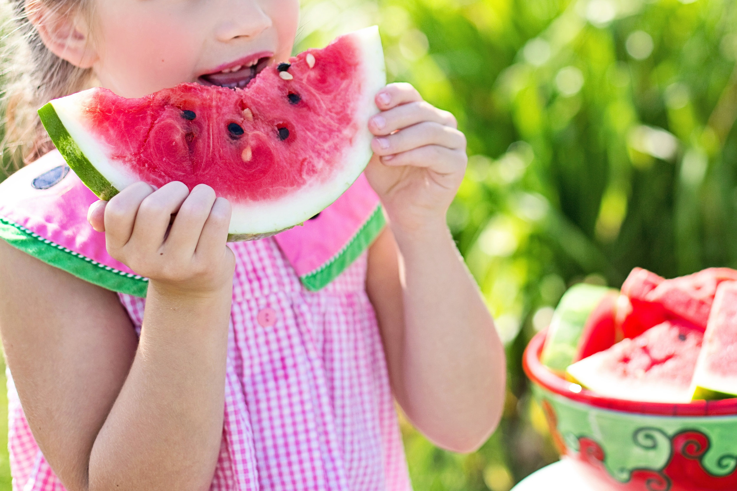 Canva - Girl Eating Sliced Watermelon Fruit Beside Table.jpg