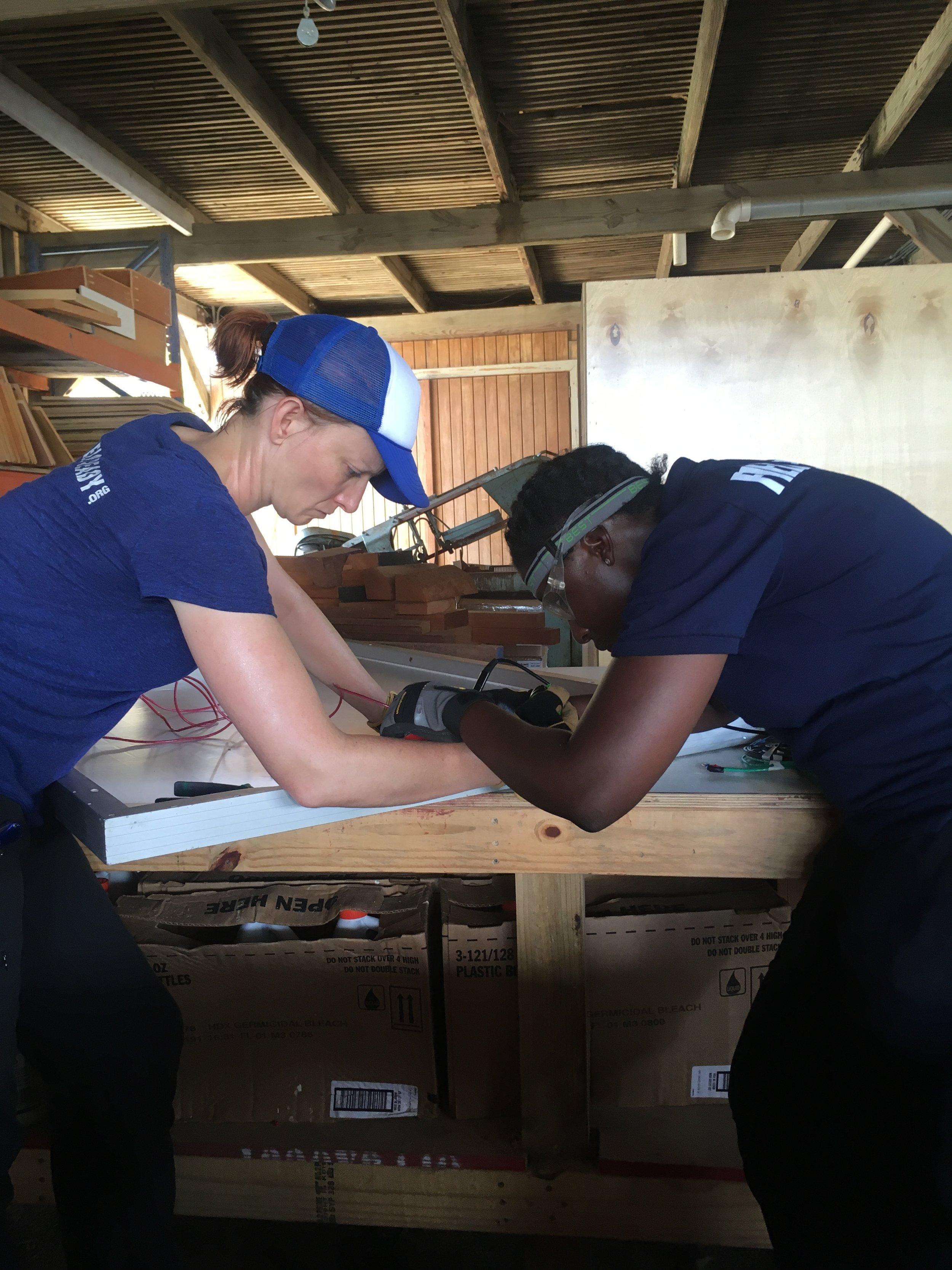 Dara and Julia soldering solar panels.JPG