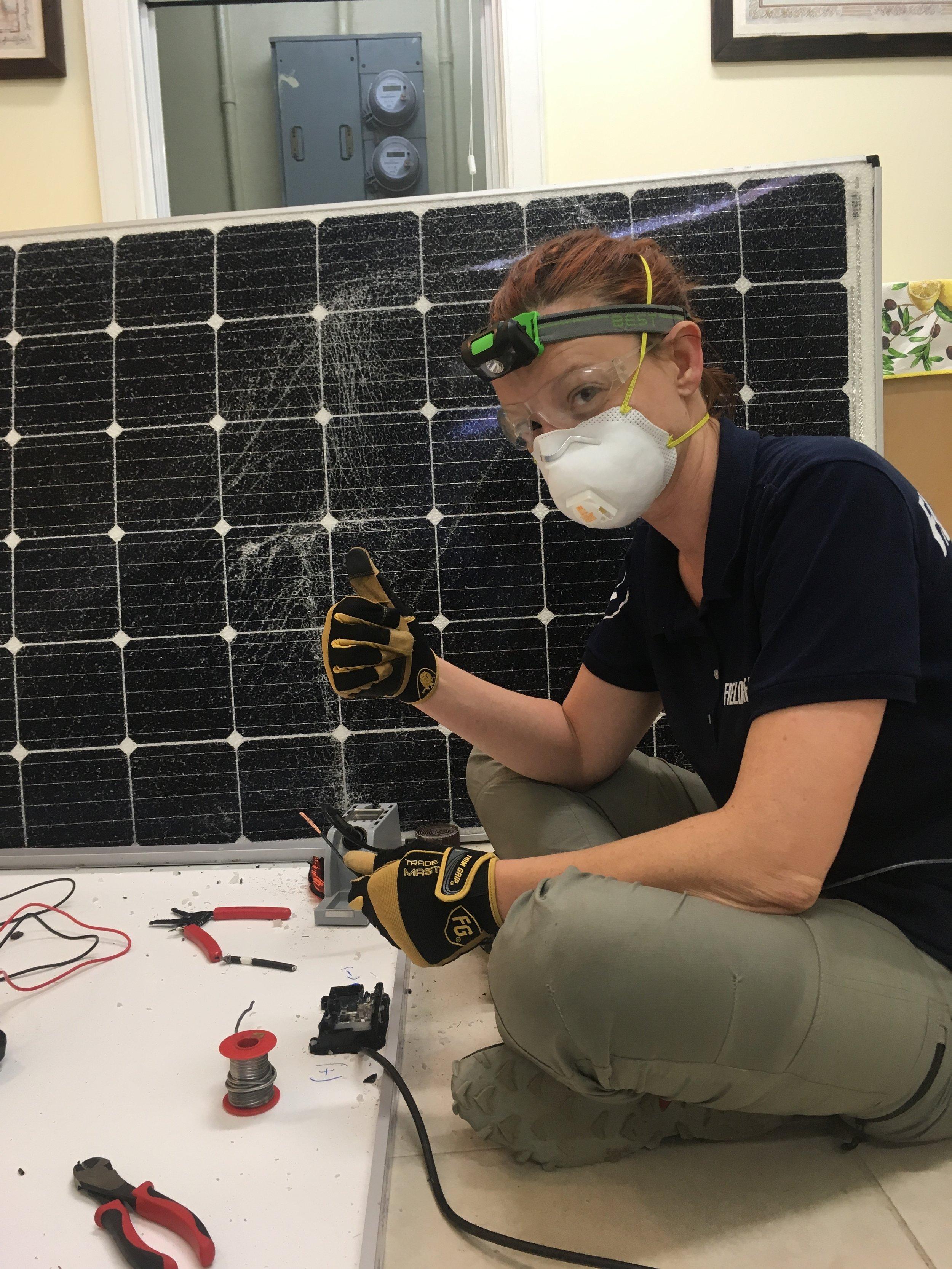 Dara soldering and reparing solar panels.JPG