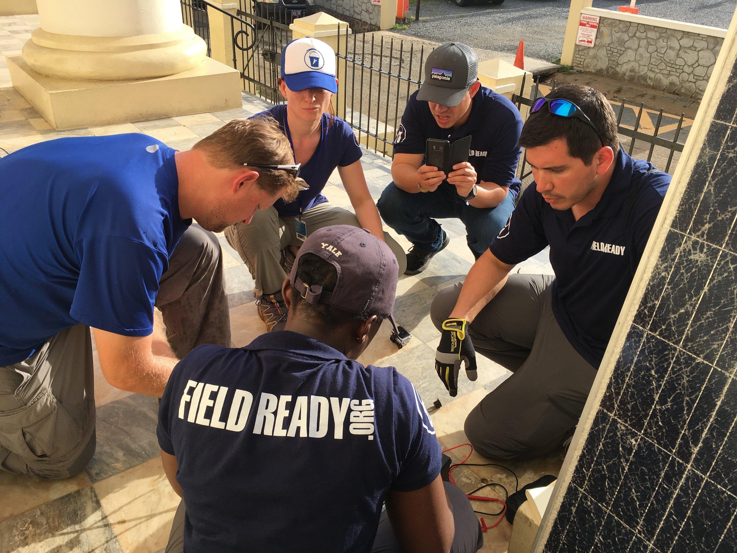 The team fixing a solar panel.JPG
