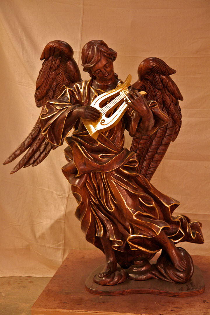 Hand carved angel with lyre.