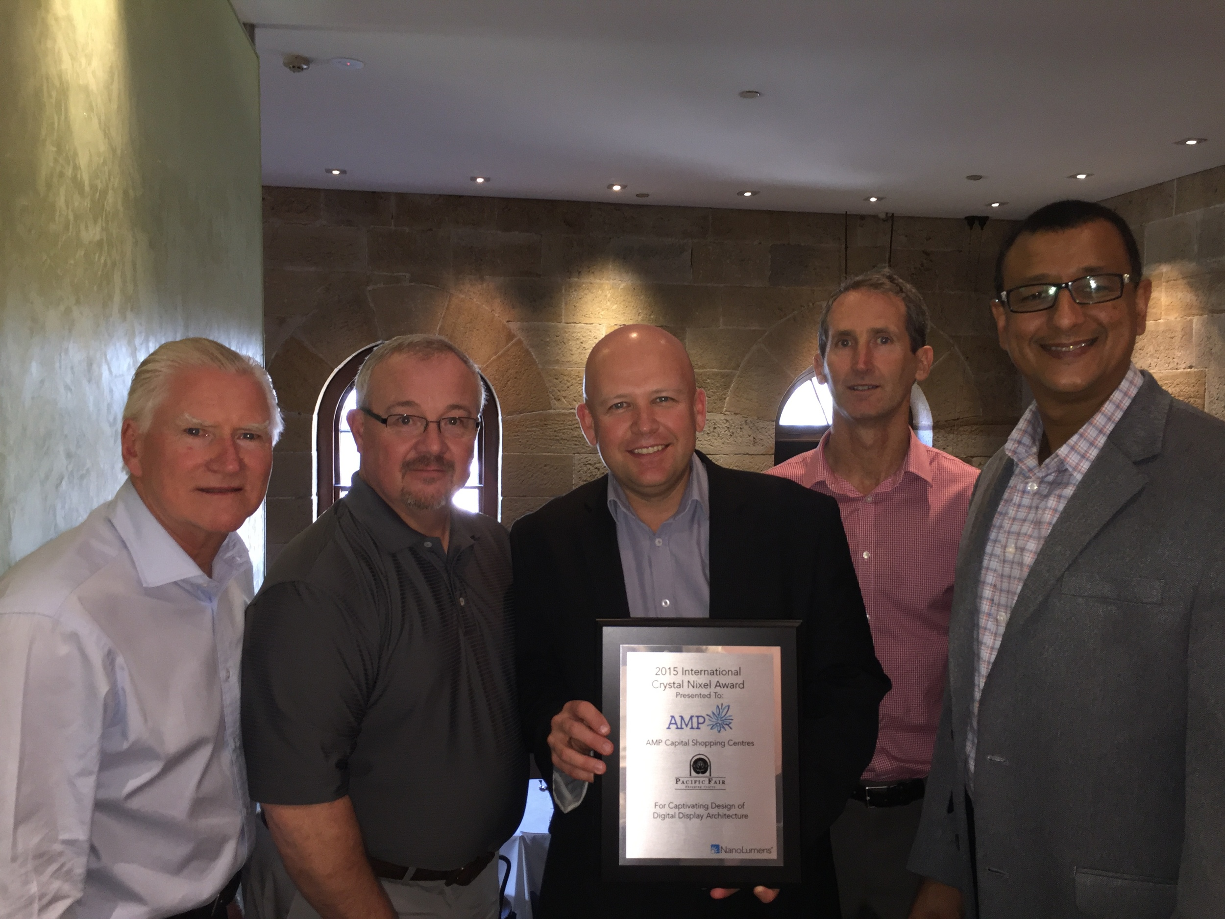 NanoLumens Vice President of Strategic Accounts Almir DeCarvalho (right) presents AMP Capital representatives with the 2015 International Crystal Nixel Award.