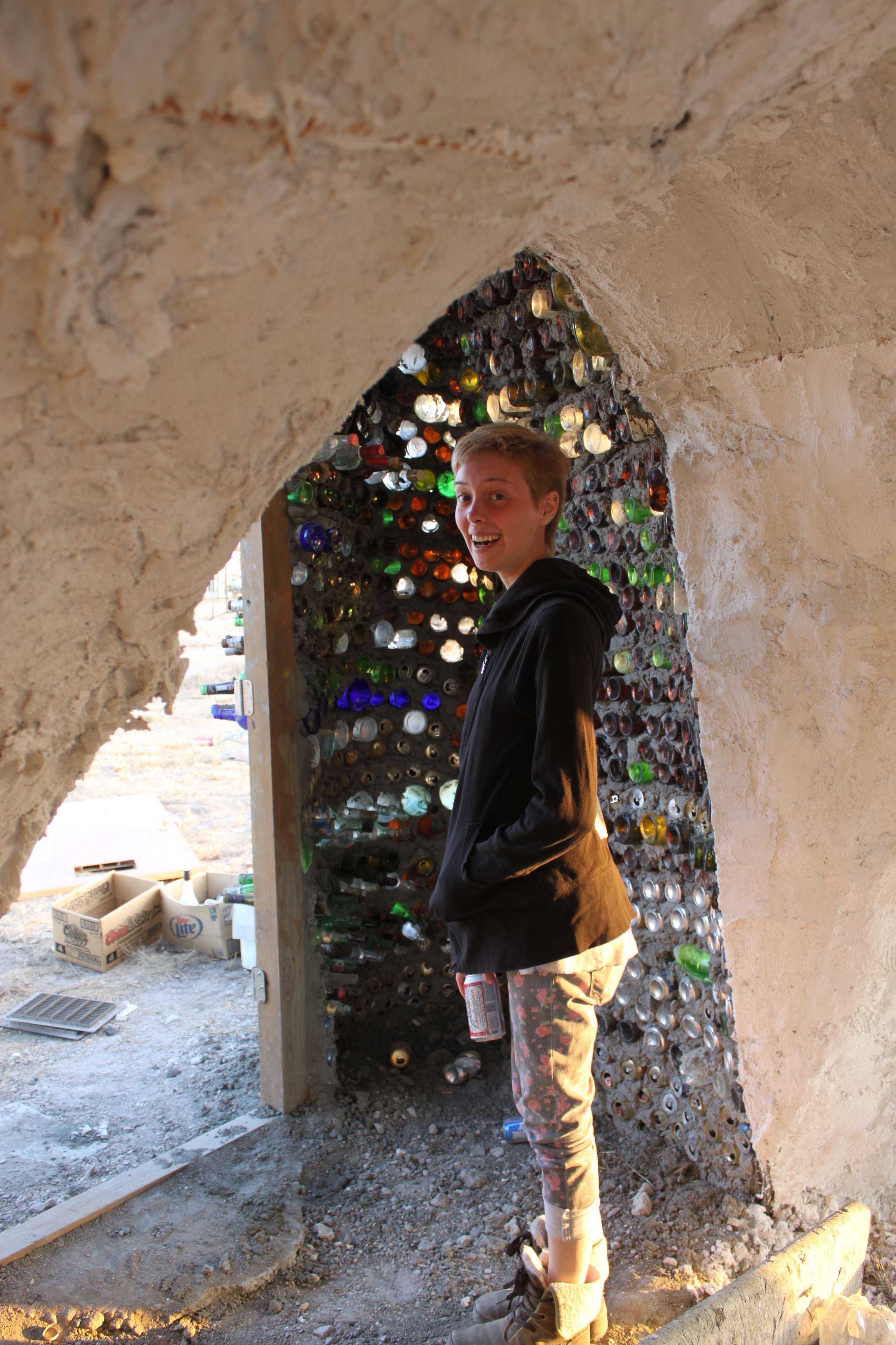 Angie in a castle of old beer cans and bottles.