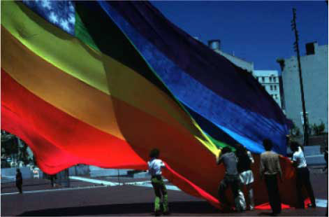 """The Original 8-color Rainbow Flag, San Francisco United Nations Plaza, June 25, 1978. Photo: James McNamara. Courtesy of the artist. Baker is third from the left """"in satin pajamas with my long hair."""""""