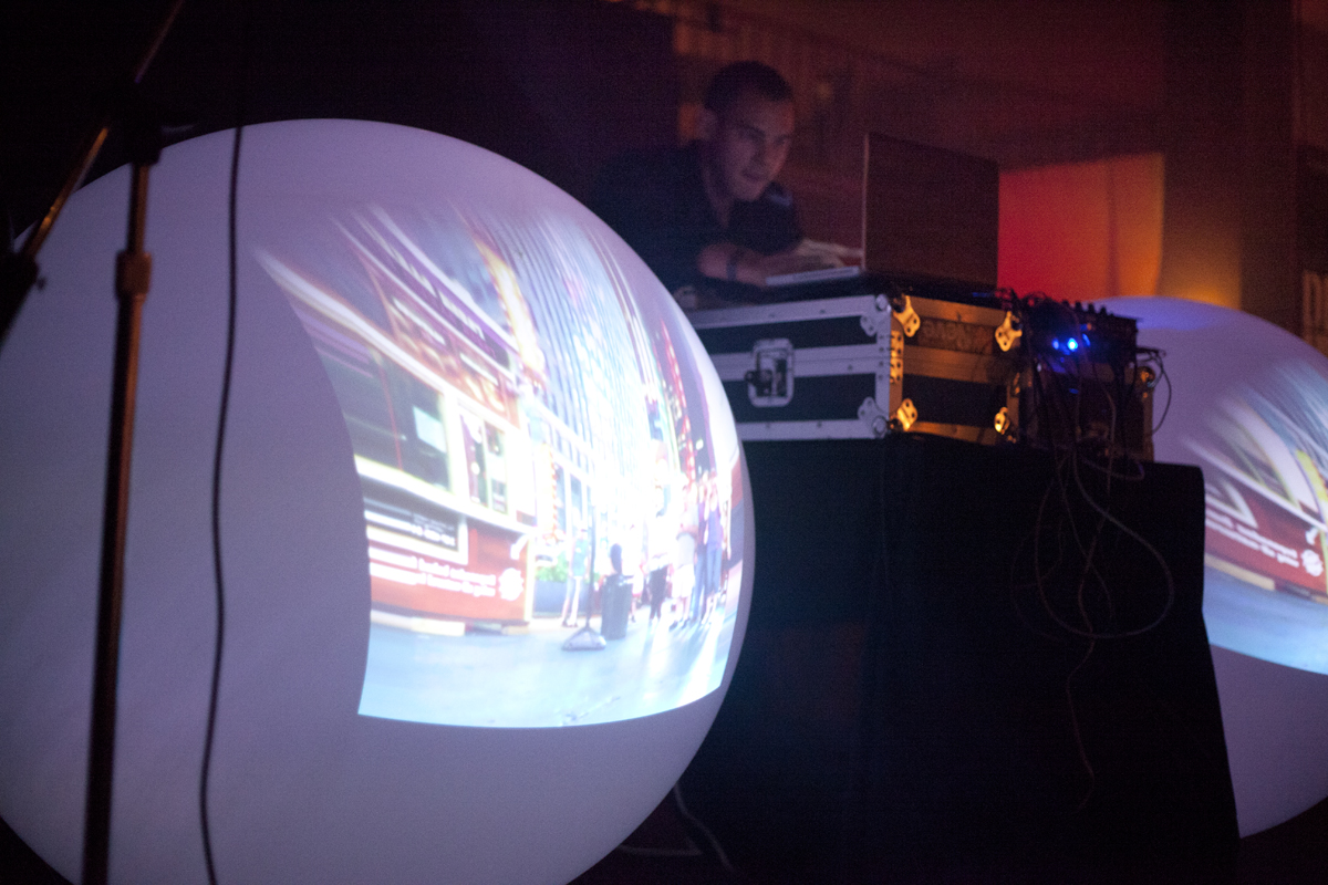 Michna live at work during a 2013 tour in which he built a portable music set-up that fit into two custom suitcases. Using two tiny projectors shooting into mirrors and reflecting onto the weather balloons, he placed a strobe underneath his DJ table that was triggered with his foot, while projecting footage of each city that he had shot earlier that day onto the balloons.