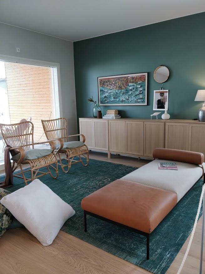 Tässä kuvasta voi poimia monia tämän hetken sisutuksen trendijuttuja: daybed, ruskea nahka,rottinkikalusteet ja vihreä sävy seinässä. Sekä myös se niin pop pyöreä peili.