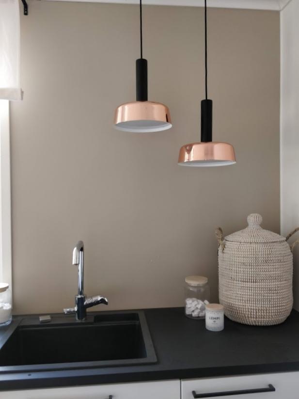 Kodinhoitohuoneen kaunis beigen sävyinen seinä ja yksityiskohtana kuparin väriset riippuvalaisimet.