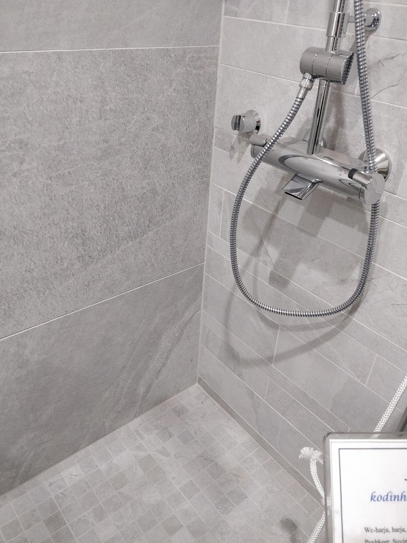 Jos ei halua kylpyhuoneessa leikitellä väreillä, voi hyvin valita erikokoisia laattoja piristämään tilan ilmettä.