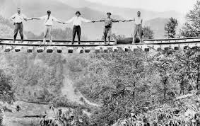 Men standing on a washed out railroad bridge