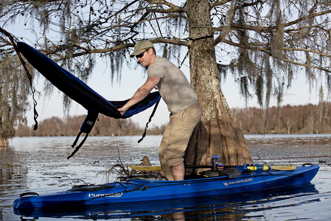 nate doing his best to climb into a hammock from a kayak