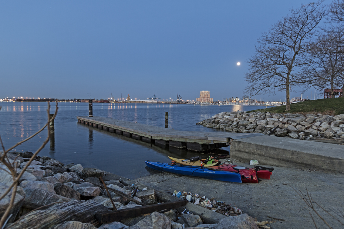 A full moon over the harbor at twilight and avoiding the trash at the city boat launch.