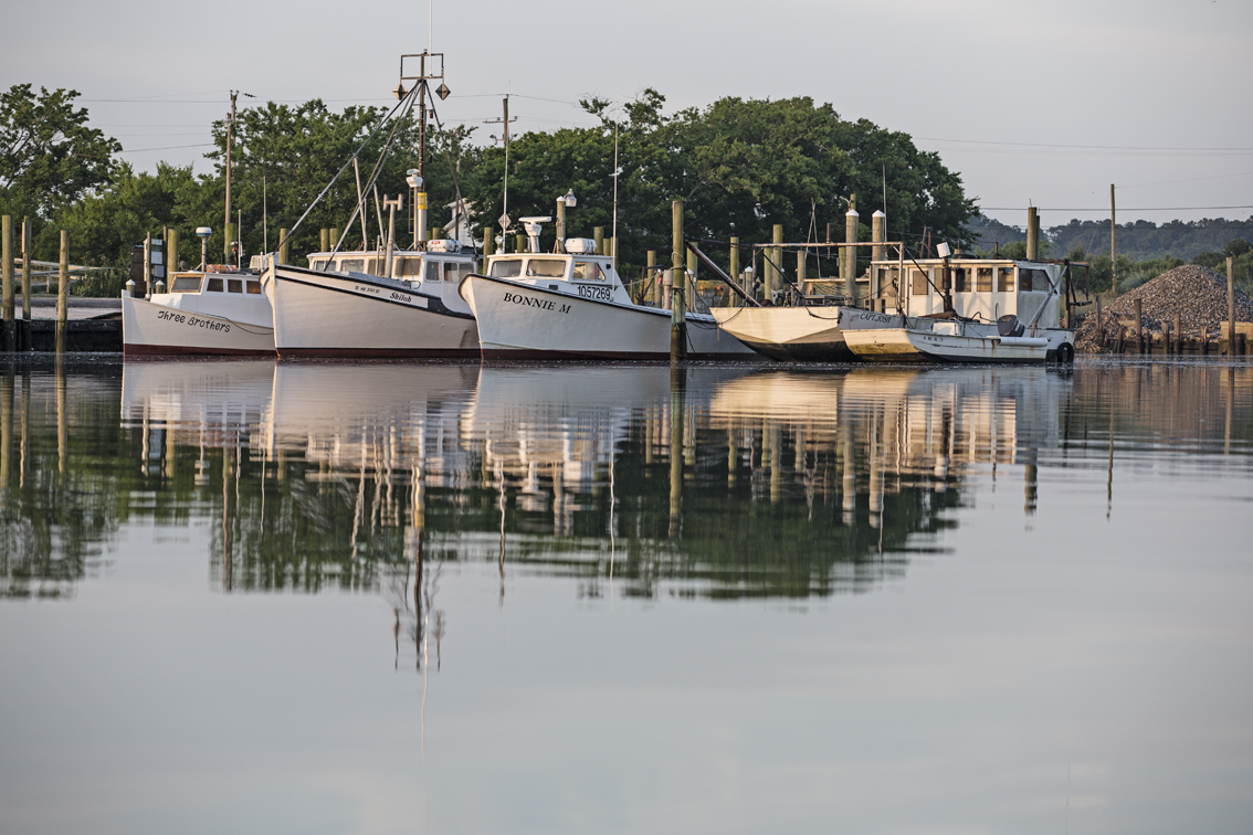 A fleet of boats in the Oyster harbor, check out that pile of oyster shells in the background.