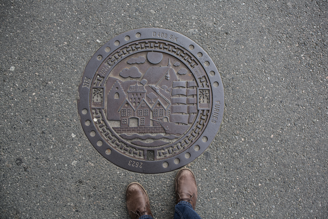 Norway has some of the best man-hole covers ever. I assume this is a scene of the Bryggen Harbor.