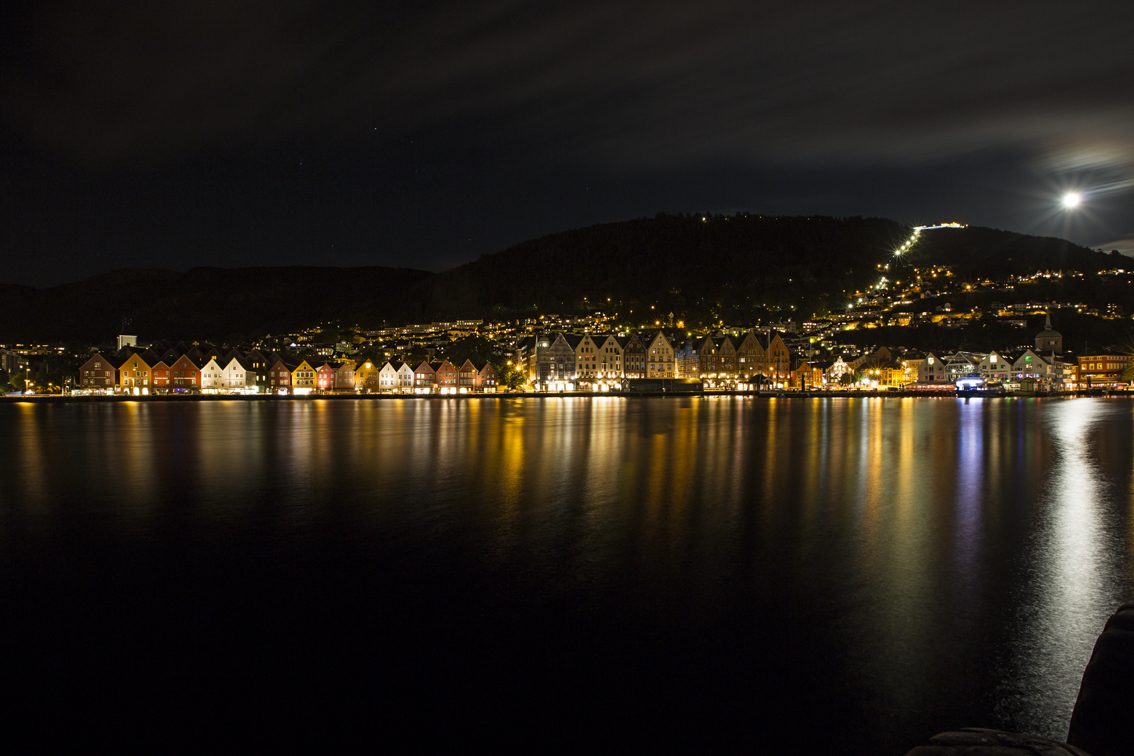 The neighborhood of Bryggen from across Bergen Harbor, with a full moon rising over Mt. Floyen.