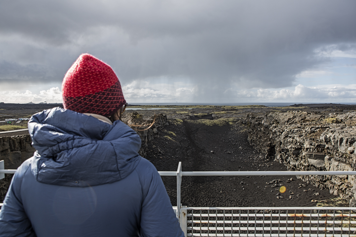 Sloane standing between the continental divide, some classic Iceland skies in the background.