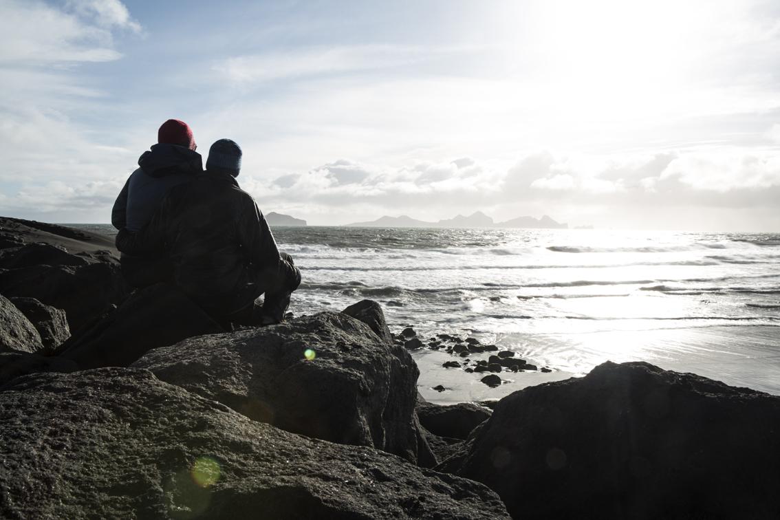 Sitting on the rocks at Landeyjahöfn harbor, in the distance is Vestmannaeyjar, a group of inhabited volcanic islands.