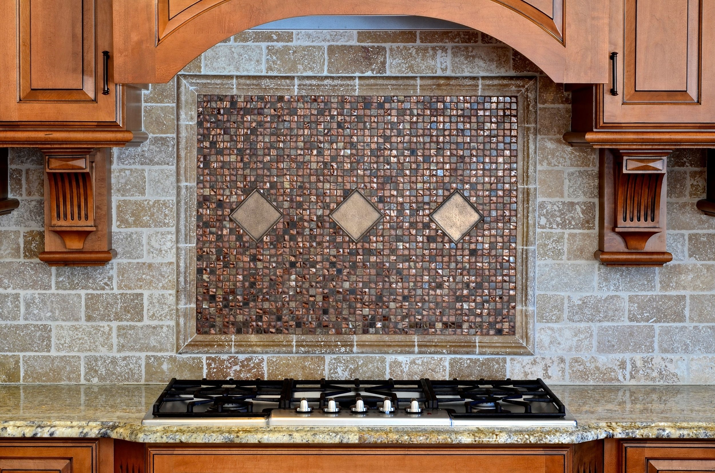 This beautiful mosaic and oiled bronze tile is an understated and elegant focal point in the cooking area.