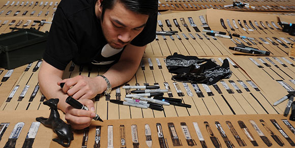 Allister Lee illustrating his massive collection of black markers.