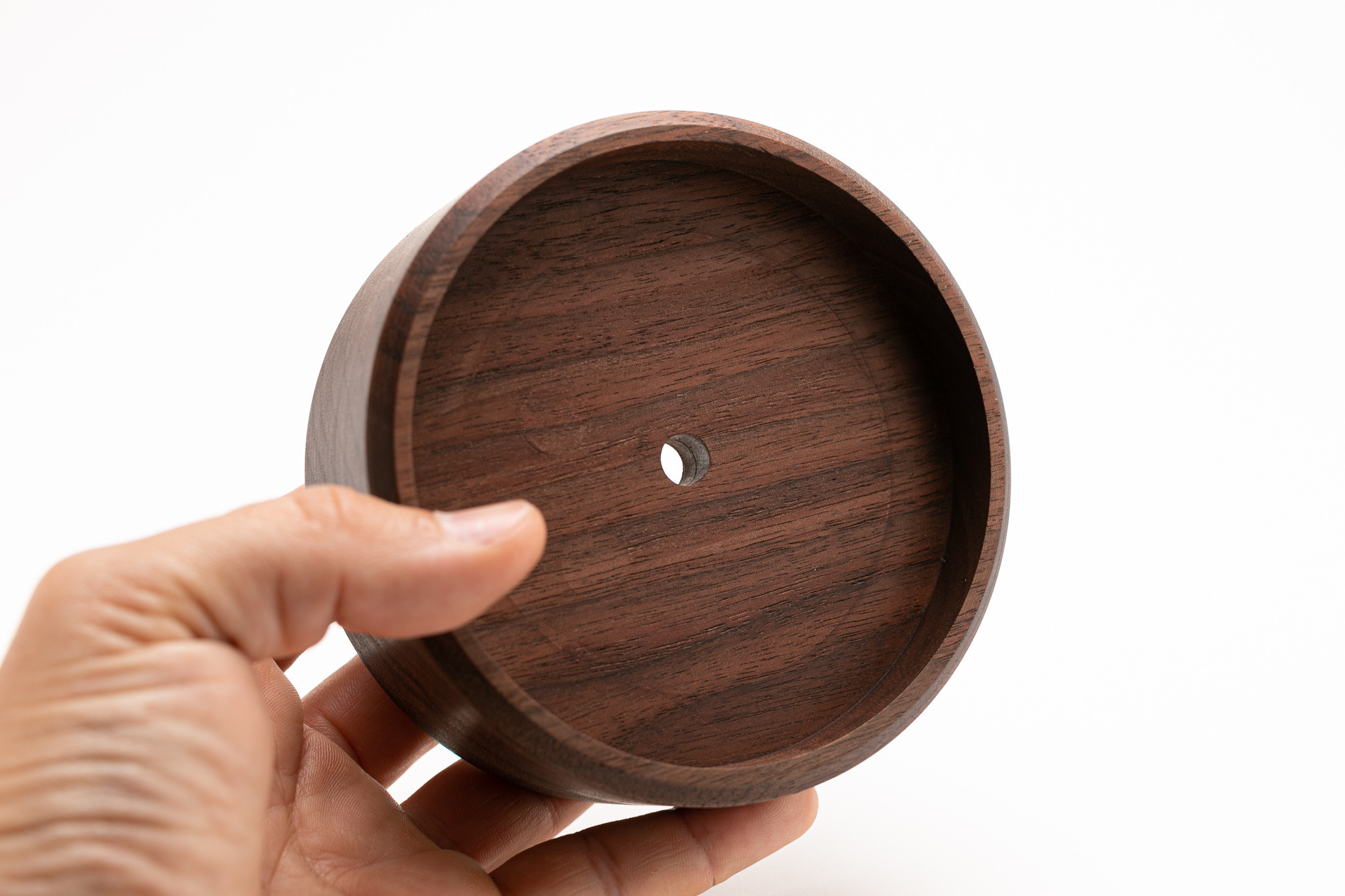 """THE BODY - –SOLID WALNUT–Hand crafted from solid hard walnut that's sustainably sourced in the USA. Just like in nature, the wood on each clock varies from piece to piece. A layer of mineral oil is applied by hand to each body, increasing the longevity of the wood's pristine condition. The body measures 4.5"""" in diameter and 1.5"""" thickness."""