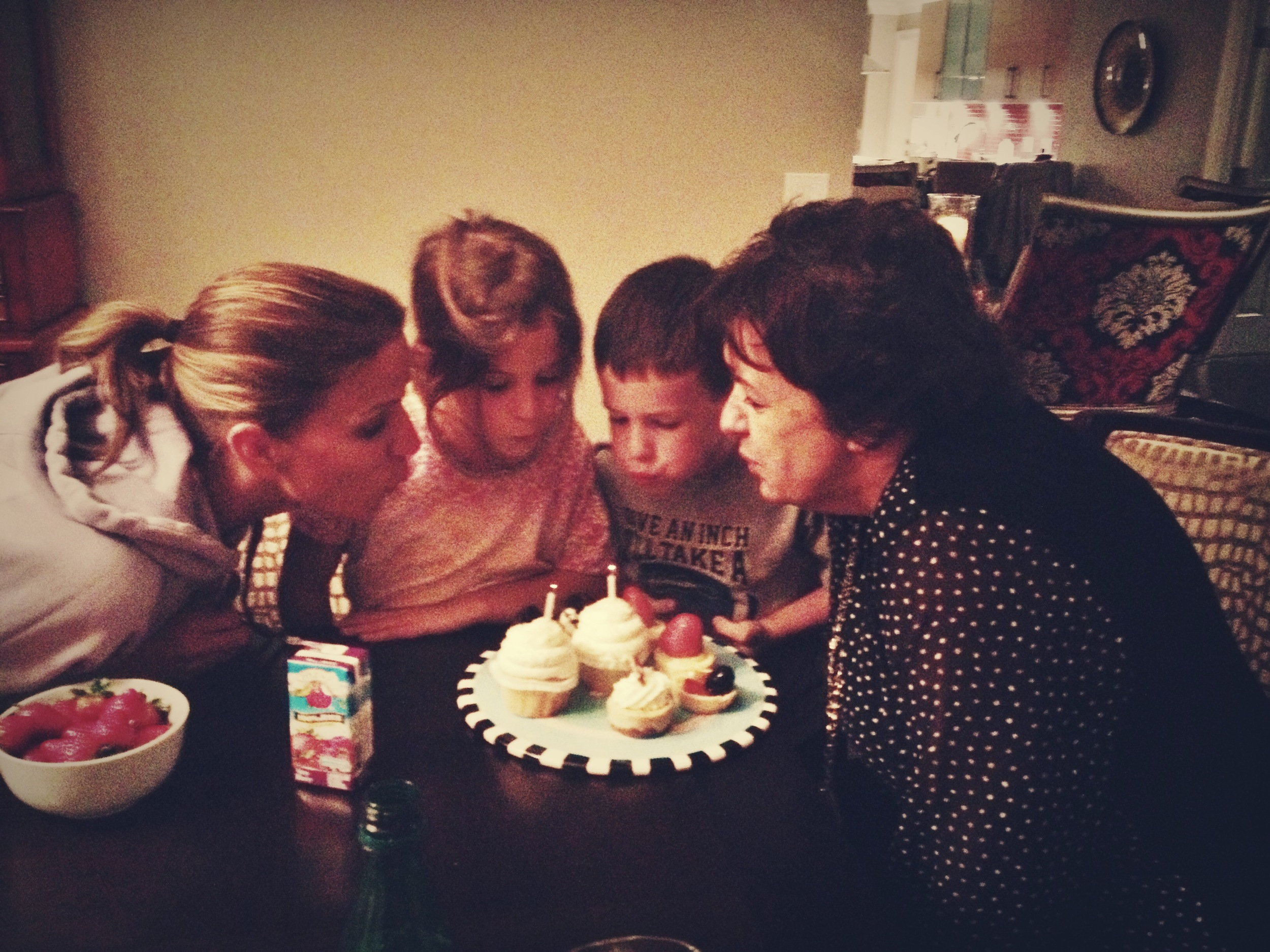 Whitney and Mom get some help from Taylor and Connor, while blowing out their birthday candles. In lieu of a cake, which would have provided lots of left overs, we went for cupcakes and small tarts with organic strawberries for dessert.