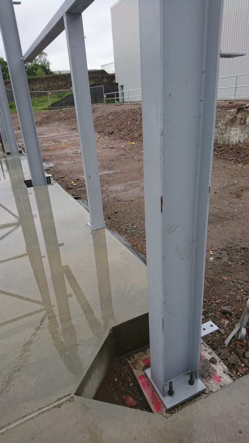 Steel beams being secured to the ground, creating a strong frame work.