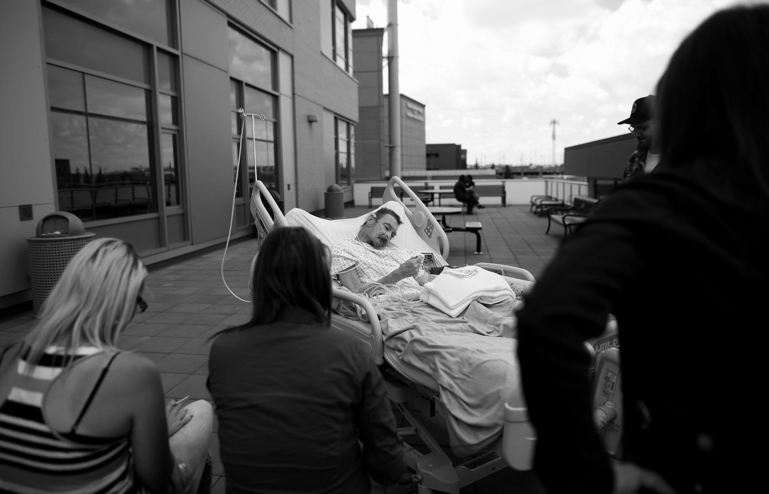 Surrounded by family and friends PJ McGrath enjoys a last smoke on the roof of the hospital where he has been the last ten months.