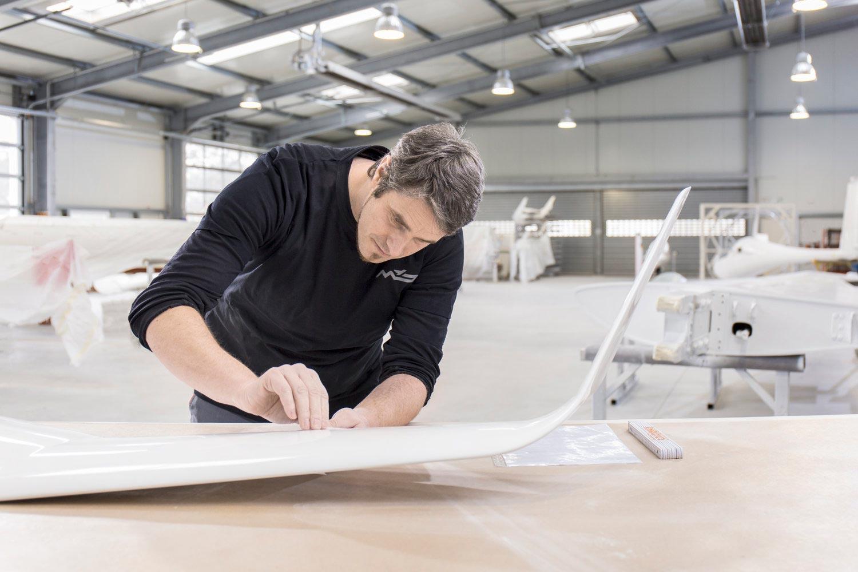 Business-Portrait im Hangar für Segelflugzeuge bei der Bearbeitung eines Flügels für die M&D Aviation Marketing Image-Kampagne