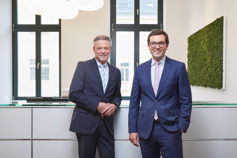 Corporate Business-Portrait der Notare Dr. Till Bremkamp und Michael Uerlings von Notariat Uerlings & Bremkamp vorm Fenster am Empfangsschalter für Image-Kamapagne