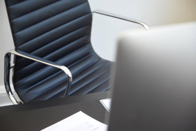 Werbefotografie eines Schreibtischstuhls vorm iMac am schwarzem Schreibtisch für Imagekamapgne des Notariats Uerlings & Bremkamp