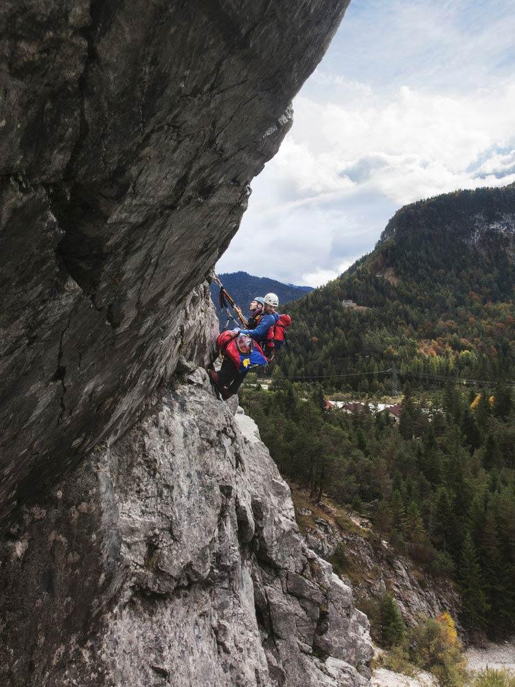 Werbefoto der DRK Bergwacht beim Rettungseinsatz in den Bergen an einer Felswand mit Kletterausrüstung für Jahreskalender